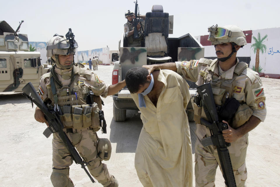Iraqi army soldiers bring in a blindfolded and handcuffed suspected al-Qaida member to detention centers in an Iraqi army base in Baghdad, Iraq, Wednesday, July 25, 2012. Iraqi security forces raided some villages in Arab Jabour, south of Baghdad, and detained 16 men suspected members of al-Qaida. (AP Photo)