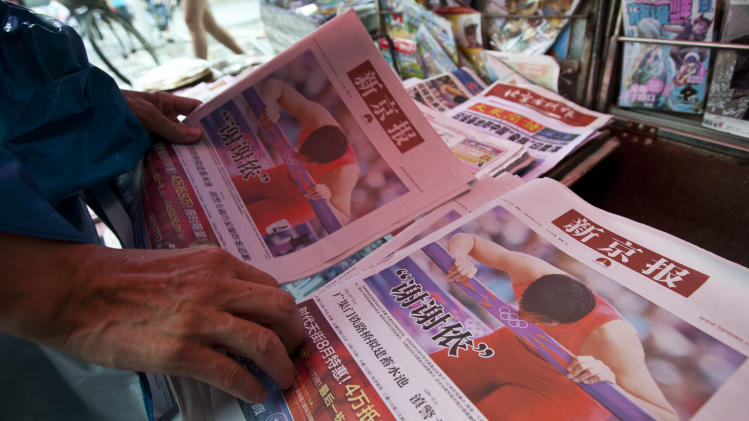 A man picks copies of a newspaper at a newsstand, where Chinese hurdler Liu Xiang's photos are seen on local papers' front pages, in central Beijing Wednesday, Aug. 8, 2012. Many Chinese following the Olympics at home called Liu Xiang their hero after the former world-record holder and 2004 Olympic champion crashed into the first hurdle during his first heat of the 110-meter hurdles on Tuesday. (AP Photo/Alexander F. Yuan)