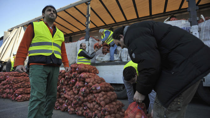 Farmers unloads sacks of potatoes from a truck for sale at cost price in the northern Greek town of Katerini, Greece on Saturday, Feb. 25 2012.  Farmers in northern Greece have joined forces with local residents to provide cheap produce to people whose family budgets have been slashed by the financial crisis, and also to help producers who say they are being squeezed by middlemen. Hundreds of families turned up Saturday in this northern Greek town to buy potatoes at massively reduced prices, sold directly by producers at cost price. (AP Photo/Nicolas Giakoumidis)