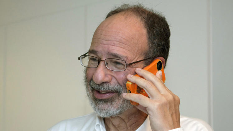 This photo provided by Stanford News Service, shows Alvin Roth taking a phone call, after being awarded the Nobel economics prize, at his home in Menlo Park, Calif. on Monday, Oct. 15, 2012.  Roth, 60, and Lloyd Shapley, 89, two American scholars, were awarded the Nobel economics prize on Monday, for studies on the match-making that takes place when doctors are coupled up with hospitals, students with schools and human organs with transplant recipients.  The work of Roth and Shapley has sparked a flourishing field of research and helped improve the performance of many markets, the Royal Swedish Academy of Sciences said.  (AP Photo/ Stanford News Service, Linda A. Cicero) MANDATORY CREDIT