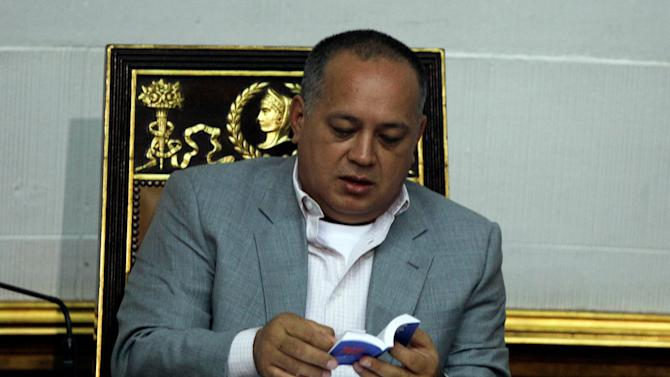 Venezuela's National Assembly President Diosdado Cabello reads a copy of the Venezuelan Constitution during a session in Caracas, Venezuela, Tuesday, Jan. 8, 2013. President Hugo Chavez won't be able to attend his scheduled swearing-in this week, Venezuela's government announced, confirming suspicions that the leader's illness will keep him in a Cuban hospital past the key date. (AP Photo/Fernando Llano)