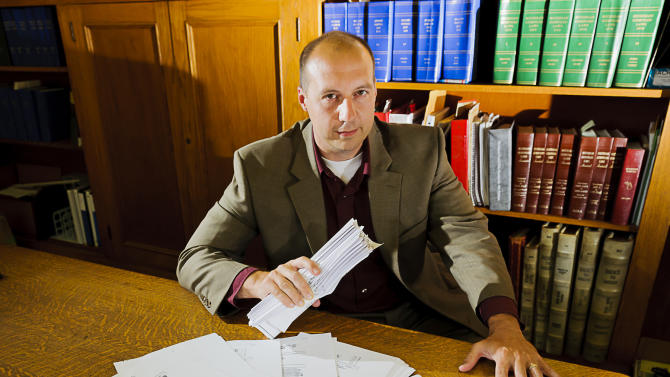 In this July 14, 2011 photo, Ingham County (of Michigan) Registrar of Deeds, Curtis Hertel, displays documents filed in Ingham County containing signatures of well-known robo-signers which are known to be fraudulent, Thursday July 14, 2011 at the Ingham County Courthouse in Mason, Michigan.  (AP Photo/Kevin W. Fowler)