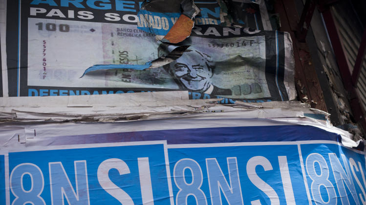 "A poster with a photo of Argentina's late President Nestor Kirchner, top, is partially covered by posters promoting an anti-government march in Buenos Aires,  Argentina,  Wednesday, Nov. 7, 2012. People are using social networks instead of political parties to mobilize a massive march for Thursday against the leadership of Argentina's President Cristina Fernandez, mobilizing what they hope will be the largest anti-government protest the country has seen in more than a decade. The poster reads in Spanish ""Yes to democracy, no to re-election."" (AP Photo/Victor R. Caivano)"