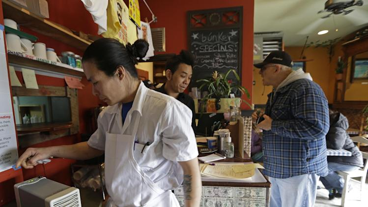 Jimmy Tu, left, a co-owner of Bunker restaurant in New York, adjusts an air purifier that he claims cleanses the air of pollutants in his Queens restaurant which is adjacent to a Superfund site on Newtown Creek, Wednesday, Feb. 20, 2013.  Neo Tanusakdi, center, rings up a customer's order. (AP Photo/Kathy Willens)