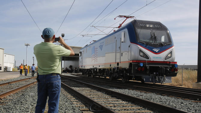 In this photo taken Saturday, May 11, 2013, Dave Ward, vice president of Locomotives for the Siemens Rail Systems,  takes a picture of one of the new Amtrak Cities Sprinter Locomotive built by Siemens  in Sacramento, Calif. The new electric locomotive, one of three of 70 to be built,  will run on the Northeast intercity rail lines and  replace Amtrak locomotives that have been in service for 20 to 30 years.(AP Photo/Rich Pedroncelli)