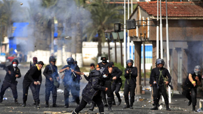 An Egyptian woman runs for cover as riot police throw stones during clashes near a state security building in Port Said, Egypt, Thursday, March 7, 2013. Clashes between protesters and police continued into a fifth day on Thursday in the restive Egyptian city of Port Said. (AP Photo/Khalil Hamra)