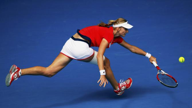 Makarova of Russia stretches to hit a return to Halep of Romania during their women's singles quarter-final match at the Australian Open 2015 tennis tournament in Melbourne