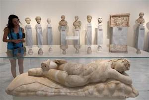 A tourist looks at a statue of a sleeping Maenad (AD…