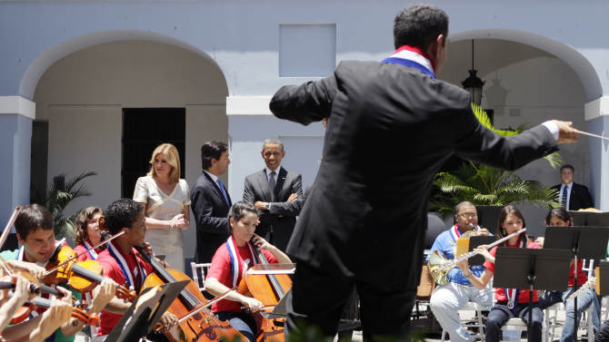 President Barack Obama stands with Gov. Luis Fortuno,  and his wife Luce Vela de Fortuno, as a youth band plays in a courtyard as he tours La Fortaleza, Tuesday, June 14, 2011, in San Juan, Puerto Rico. (AP Photo/Carolyn Kaster)