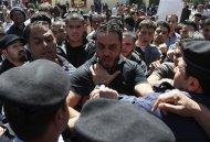 A Palestinian protester scuffles with policemen during a demonstration against U.S. President Barack Obama in the West Bank city of Ramallah March 21, 2013. REUTERS/Mussa Qawasma
