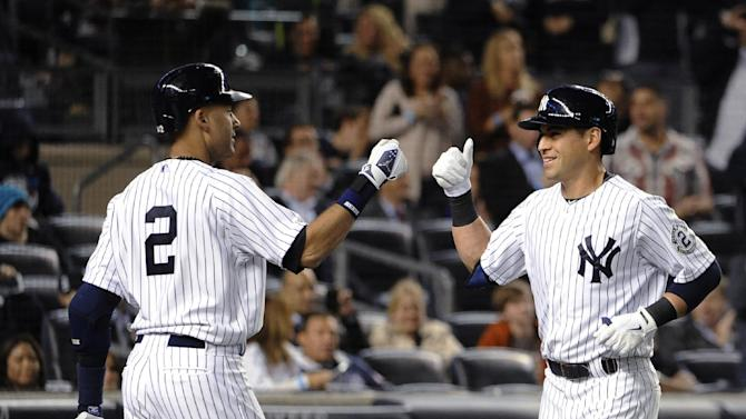 New York Yankees' Derek Jeter (2) greets Jacoby Ellsbury at home plate after Ellsbury hit a two-run home run off of Blue Jays starting pitcher Mark Buehrle in the third inning of a baseball game at Yankee Stadium on Friday, Sept. 19, 2014, in New York. (AP Photo/Kathy Kmonicek)
