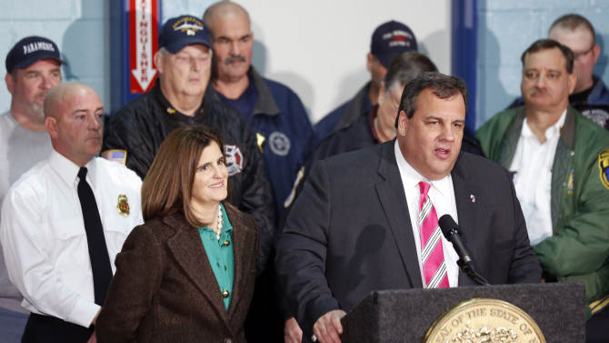 """New Jersey Gov. Chris Christie, right, stands next to his wife, Mary Pat Christie, left, and a group of first responders while talking during a news conference at at fire house, Monday, Nov. 26, 2012, in Middletown, N.J. Christie announced he will seek re-election to a second term. Christie says he want New Jerseyans to know that he's """"in this for the long haul"""" as he leads the state's recovery from Superstorm Sandy.  (AP Photo/Julio Cortez)"""