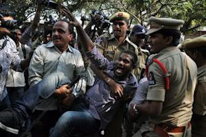 Indian police personnel detain a member of The All …