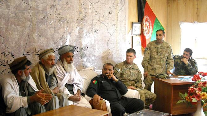 "In this March 26, 2013, photo, Afghan elders express relief that the force that raided their villages overnight was mostly Afghan, hours after a combined force of roughly 1,250 Afghans and 175 Americans encircled the town in a pre-dawn raid.  U.S. Brigade commander Col. Joseph ""J.P."" McGee, of the U.S. Army's 1st Brigade Combat Team, 101st Airborne Division, listens, with his U.S. translator, standing, and the Afghan police and army commanders listening at the Afghan army base next to Forward Operating Base Connolly in Khogyani district, Nangarhar province, east of Kabul, Afghanistan. U.S. commanders trying to hand off war-fighting responsibility by the end of 2014 are encouraged by the uneven yet steady progress of fledgling Afghan security forces. (AP Photo/Kim Dozier)"