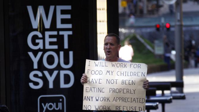 File photo of an unemployed man holding a sign asnd asking for work as he stands on a footpath in central Sydney