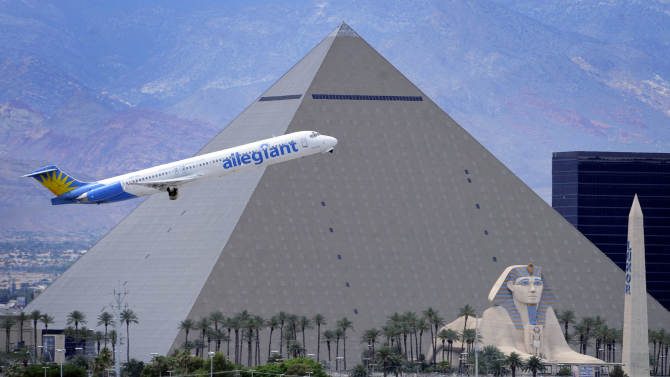 In this Thursday, May 9, 2013, photo, An Allegiant Air jetliner flies by the Luxor Resort & Casino after taking off from McCarran International Airportm in Las Vegas. While other U.S. airlines have struggled with the ups and downs of the economy and oil prices, tiny Allegiant Air has been profitable for 10 straight years. (AP Photo/David Becker)