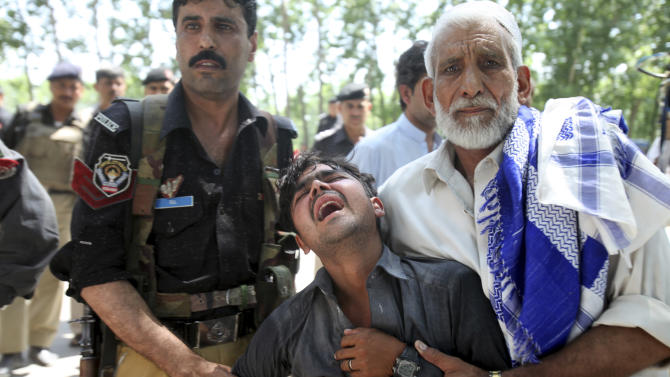A Pakistani man, center, reacts after learning of the death of his brother at the site of a bus explosion on the outskirts of Peshawar, Pakistan, Friday, June 8, 2012. A bomb tore through a bus carrying government employees and other civilians in northwestern Pakistan on Friday, killing several people in an attack that served as a reminder of the continued militant threat despite a significant drop in violence over the past year, officials said. (AP Photo/Mohammad Sajjad)