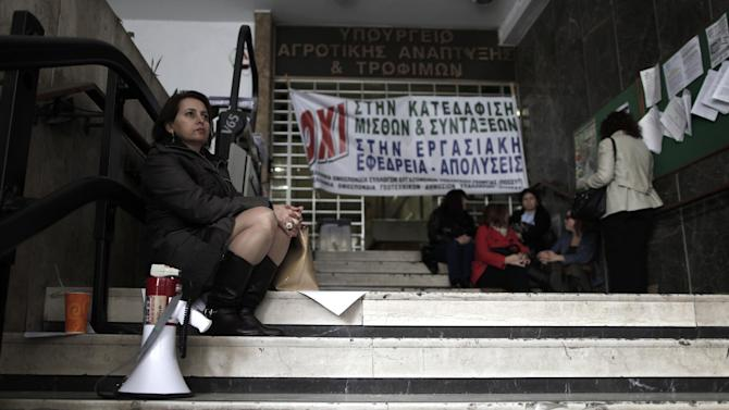 """Agriculture ministry workers are seen at the entrance to the ministry headquarters in Athens, which was occupied by protesting employees on Monday, Nov. 19, 2012. The banner reads """"No to the demolition of salaries and pensions."""" Civil service unions are up in arms over government plans to place 2,000 state employees on notice ahead of reassignment or potential dismissal. (AP Photo/Petros Giannakouris)"""