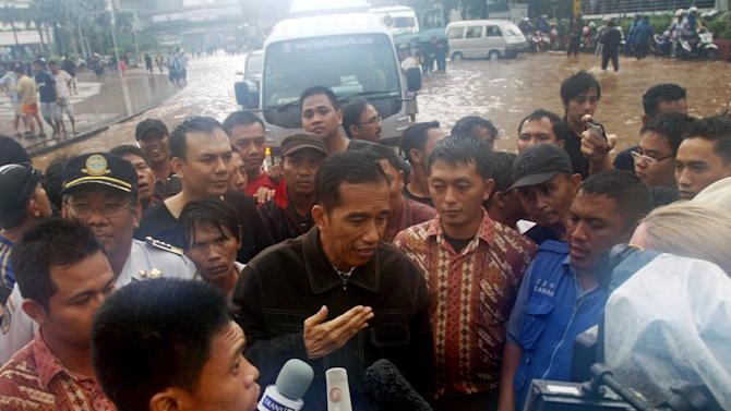 In this photo taken Thursday, Jan. 17, 2013, Jakarta Gov. Joko Widodo, center, talks with journalists during a visit to a flooded area in Jakarta, Indonesia. Cheering crowds greeted the new leader of this Asian megacity as he toured its flooded business district atop a handcart typically used to haul garbage. Widodo's trip through his inundated city of 14 million reflected his hands-on approach to leadership, a style that helped him win election in September against an incumbent who was backed by the establishment political parties. (AP Photo/Achmad Ibrahim)