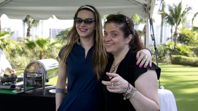 "Nania G, from the ""Bitchin' Kitchen"", left, and Alex Guarnaschelli pose for photos in Nania G's food station in Miami Beach, Fla. Saturday, Feb. 23, 2013, during a golf tournament.  Jose Andres, Todd English, Ming Tsai and Alex Guarnaschelli are among the roster of A-list chefs taking to the links during the South Beach Wine and Food Festival. (AP Photo/J Pat Carter)"