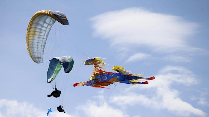 "Paragliders perform a demonstration flight during the masquerade contest of the 41st Icare Cup paragliding festival in Saint Hilaire du Touvet, French Alps, Saturday, Sept. 20, 2014. The ""Coupe Icare"" dedicated to free flight, orchestrates all the various types of flying such as hang gliding, paragliding and acrobatic sailplaneing. (AP Photo/Francois Mori)"