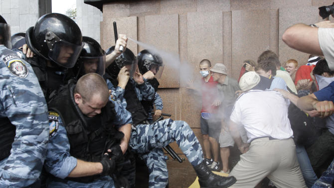 Riot police spray tear gas against opposition protesters in front of the Ukrainian House in central Kiev, Ukraine, Wednesday, July 4, 2012. Opposition activists have clashed with riot police  during a protest against a controversial bill that would allow the use of Russian in official settings in Russian-speaking regions. (AP Photo/Efrem Lukatsky)