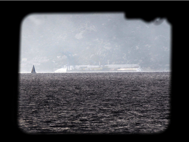 The Costa Concordia cruise ship, seen through a ferry window, leans on its side of the Tuscan Island Isola del Giglio, Italy, Saturday, Jan. 12, 2013. More time and money will be needed to remove the