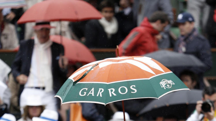 Spain's Rafael Nadal leaves the court as rain delays his match against Serbia's Novak Djokovic during their men's final in the French Open tennis tournament at the Roland Garros stadium in Paris, Sunday, June 10, 2012.  (AP Photo/Bernat Armangue)