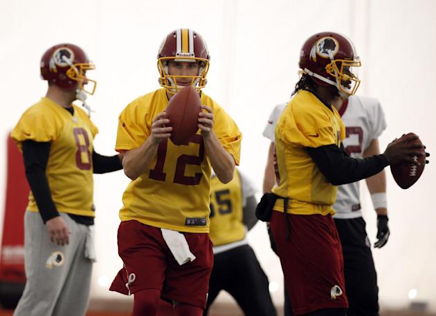Washington Redskins quarterbacks Rex Grossman, left, Kirk Cousins, center, and Robert Griffin III work during their NFL football practice Wednesday, Dec. 11, 2013, in Ashburn, Va. Cousins will start f