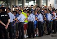 Police form a line in front of a cordon as Shanghai Shenhua fans shout to welcome former Chelsea football star Didier Drogba upon his arrival at Pudong international airport in Shanghai on July 14. Drogba was given a hero's welcome as he arrived in China to start a two-and-a-half year contract that is expected to make him one of football's highest-paid players