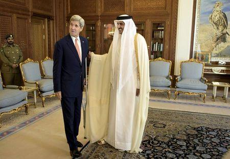 U.S. Secretary of State Kerry talks with Qatar's Emir Sheikh Tamim before their meeting at the Diwan Palace in Doha