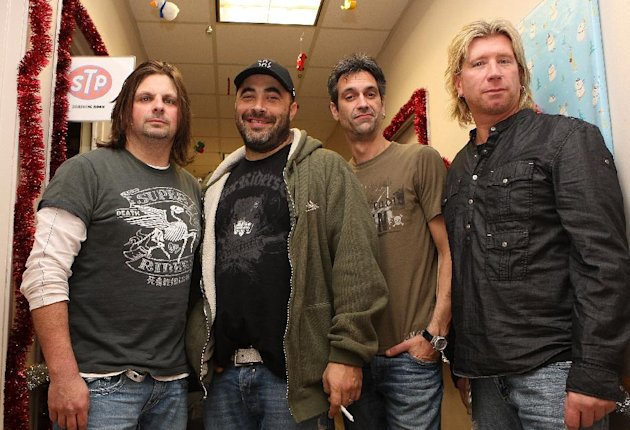 FILE - In this Dec. 13, 2012 photo, The Band Staind poses for a photograph at the KROQ Almost Acoustic Christmas held at the Gibson Amphitheater in Universal City California. An ambulance company that serves six rural western Massachusetts towns has purchased a new ambulance thanks to a $150,000 gift from the bass player for the hard rock band Staind. The gift from Johnny April enabled Highland Ambulance to buy a new vehicle to replace its aging 1998 model.(AP Photo/Shea Walsh)
