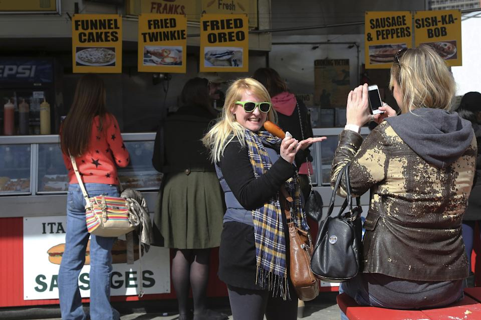 In a Saturday March 30, 2013, photo  a visitor to New York's Coney Island poses holding a corn dog.  Despite making the traditional Palm Sunday opening, many of the seasonal businesses at Coney Island are still reeling from the aftermath of Superstorm Sandy. (AP Photo/Mary Altaffer)