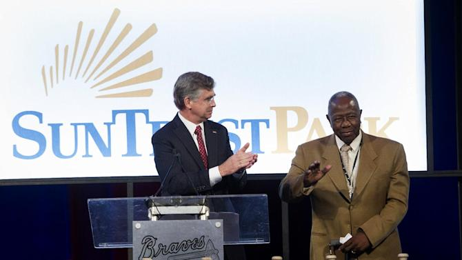 SunTrust CEO William Rogers introduces Hall of Fame baseball player Hank Aaron during a ground breaking ceremony for the Atlanta Braves new stadium which will be called SunTrust Park, Tuesday, Sept. 16, 2014, in Atlanta. The Braves will be moving from Turner Field in Fulton County to the new stadium being built in Cobb County in 2017. (AP Photo/John Amis)
