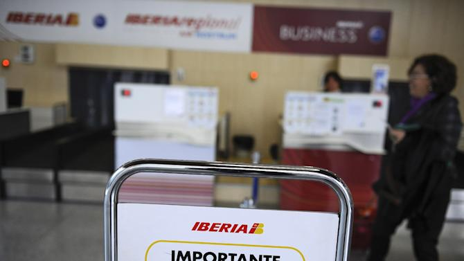 "A notice sign for Iberia airline advising passengers on permitted hand luggage dimensions is seen next to check-in counters at Noain airport, near Pamplona, northern Spain, Friday, Nov. 9, 2012. International Airlines Group warned on Friday that its Spanish carrier Iberia was ""in a fight for survival"" and unveiled a restructuring plan to cut 4,500 jobs as it reported a drop in third-quarter profit. (AP Photo/Alvaro Barrientos)"