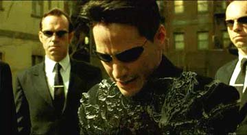 Multiple Agent Smiths ( Hugo Weaving ) attack Neo ( Keanu Reeves ) in Warner Brothers' The Matrix: Reloaded
