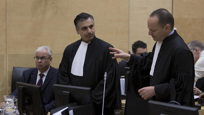 Representatives of Libya, Ahmad Sadeq Al Gehani, left, and Payam Akhavan, center, and Phillippe Sands, right, discuss at the start of a hearing of the  International Criminal Court on Libya's challenge to the admissibility of the case against Seif Al-Islam Gaddafi in The Hague, Netherlands, Tuesday Oct. 9 2012. The International Criminal Court is holding a two-day hearing into where the eldest son of former Libyan dictator Moammar Gadhafi should be put on trial. Seif al-Islam Gadhafi is charged by the international court with crimes against humanity for his alleged involvement in the deadly crackdown on dissent against his father's rule. However Libyan authorities say they want to prosecute him at home, where he is being held. (AP Photo/Michael Kooren, POOL)