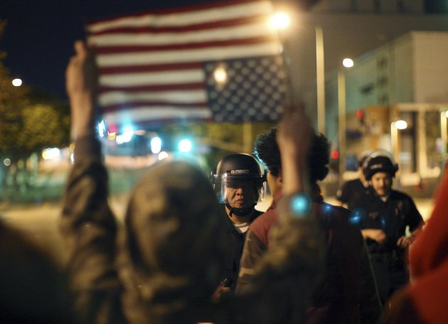 A man holds flag in the upside-down distress position before police near the Occupy Los Angeles encampment at City Hall Park shortly before the midnight deadline for eviction from City Hall Park passe