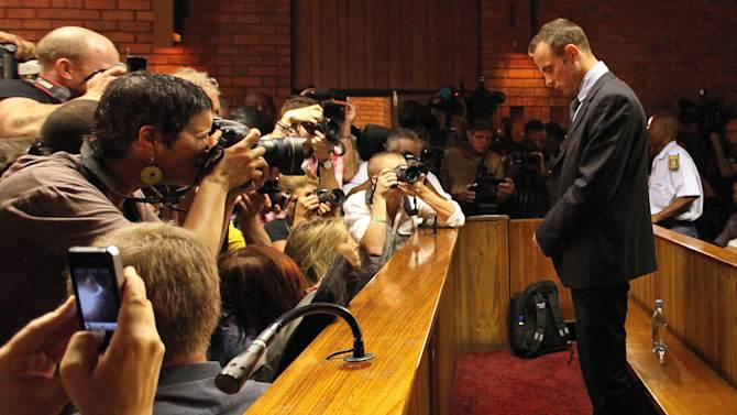 File - In this Wednesday, Feb. 20, 2013 file photo Olympic athlete Oscar Pistorius stands inside the court as a police officer looks on during his bail hearing at the magistrate court in Pretoria, South Africa. Pistorius will defend himself against a charge of premeditated murder in the slaying of his girlfriend Reeva Steenkamp, by arguing he believed he was acting lawfully and in self-denense when he fired four shots through a bathroom door in his home with his licensed 9mm handgun, criminal and firearm experts say, even though the Olympic athlete concedes now that he made a deadly error. (AP Photo/Themba Hadebe, File)