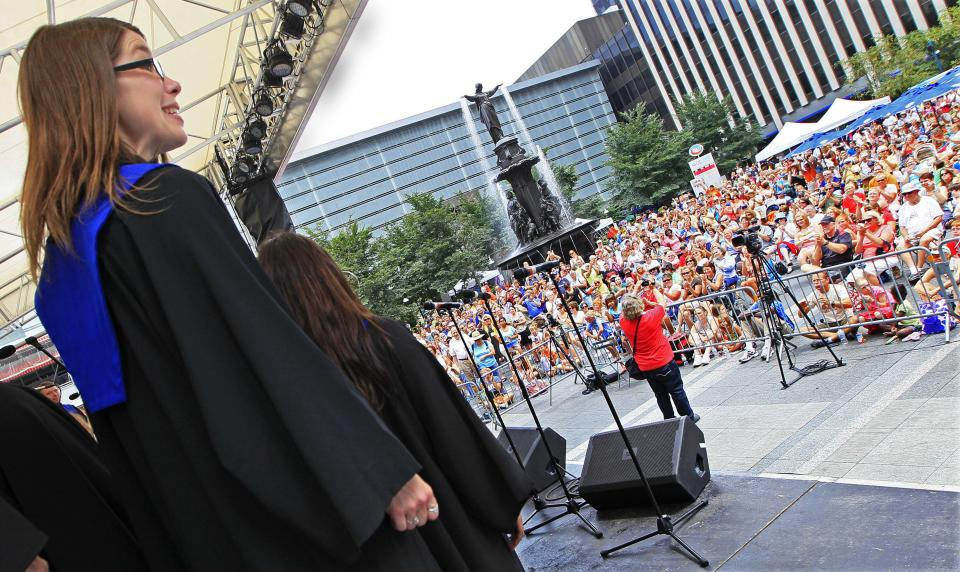 In this Thursday, July 12, 2012 photo, members of Gospelchoir Rejoice, from Langenberg, Germany, perform in front of a large crowd, on Fountain Square in Cincinnati. Hundreds of choirs from around the world are competing in 23 categories in the event that ends Saturday. (AP Photo/Al Behrman)