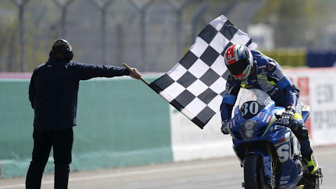 Suzuki rider Vincent Philippe of France celebrates after crossing the finish line in first position during the 38th Le Mans 24 Hours motorcycling endurance race in Le Mans