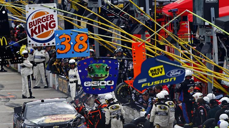 Crew members work on Tony Stewart's car during the NASCAR Sprint Cup Series Food City 500 auto race on Sunday, March 17, 2013, in Bristol, Tenn. (AP Photo/Wade Payne)