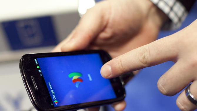A person tries a smartphone loaded with Google Wallet at the National Retail Federation, Tuesday, Jan. 17, 2012 in New York. (AP Photo/Mark Lennihan)