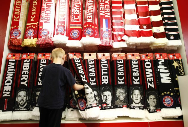 Young boy looks at fan scarves with emblems of German Bundesliga first division soccer club Bayern Munich in fan shop in Munich