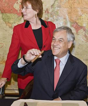 In this photo released Sunday Oct. 17, 2010, by Britain's Imperial War Museum (IWM), showing the granddaughter of former British Prime Minister Sir Winston Churchill, Celia Sandys and Chilean President Sebastian Pinera, as he sits in Sir Winston's chair and holds a display cigar, while he tours the Map Room inside the Cabinet War Rooms in central London Sunday Oct. 17, 2010. (AP Photo / IWM) ** NO SALES **