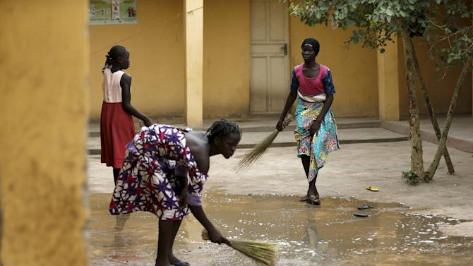 Women clean their premises at the Malkohi camp for Internally Displaced People camp in Yola, Adamawa State, Nigeria