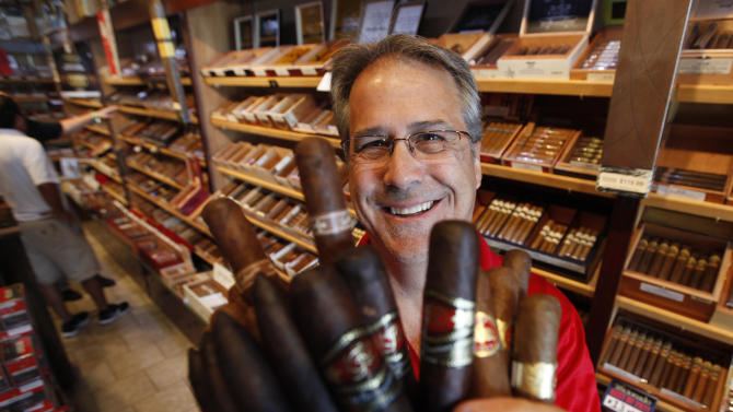 """The owner of Havana Connections cigar shop, George """"Shorty"""" Koebel, holds a bunch of cigars at his store in Richmond, Va., Wednesday, June 20, 2012.  The Food and Drug Administration intends to regulate cigars under a 2009 law that gave it authority over the tobacco industry and cigar makers and aficionados are pushing to ensure their livelihoods and the products they enjoy. (AP Photo/Steve Helber)"""