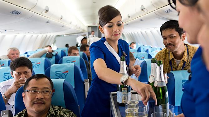 In this photo released by Sergey Dolya, cabin crew serve passengers during a flight over Jakarta, Indonesia, Wednesday, May 9, 2012. The Russian-made Sukhoi jet plane with 50 people on board, including eight Russians and an American, has gone missing during the second demonstration flight of the day near Jakarta, Indonesian government officials said Wednesday.(AP Photo/Sergey Dolya) NO SALES