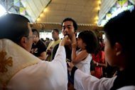 "Catholics attend a mass in a small church in Manila on April 21, 2013. A survey in February this year by the Social Weather Stations also found waning religiosity among those who classify themselves as Catholics, with only 29 percent considering themselves ""very religious"""