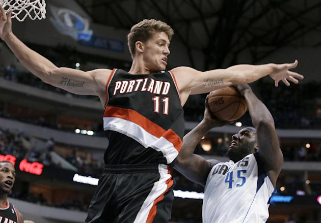 Portland Trail Blazers center Meyers Leonard (11) denies Dallas Mavericks' DeJuan Blair (45) a shot attempt during the second half of an NBA basketball game, Saturday, Jan. 18, 2014, in Dallas. Th